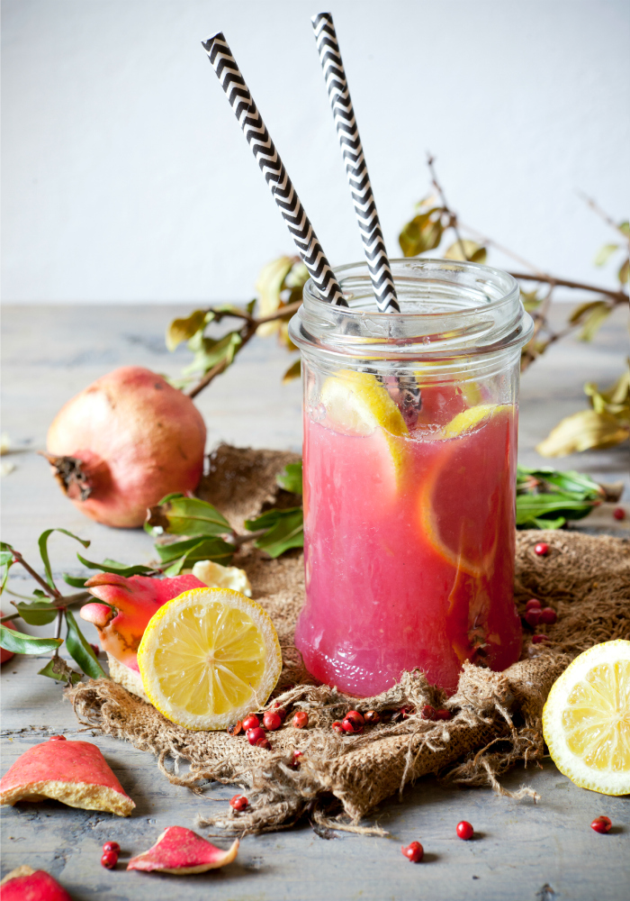 pomegranate and lemon smoothie on glass jar with two striped straw on rustic background with lemon slices and burlap